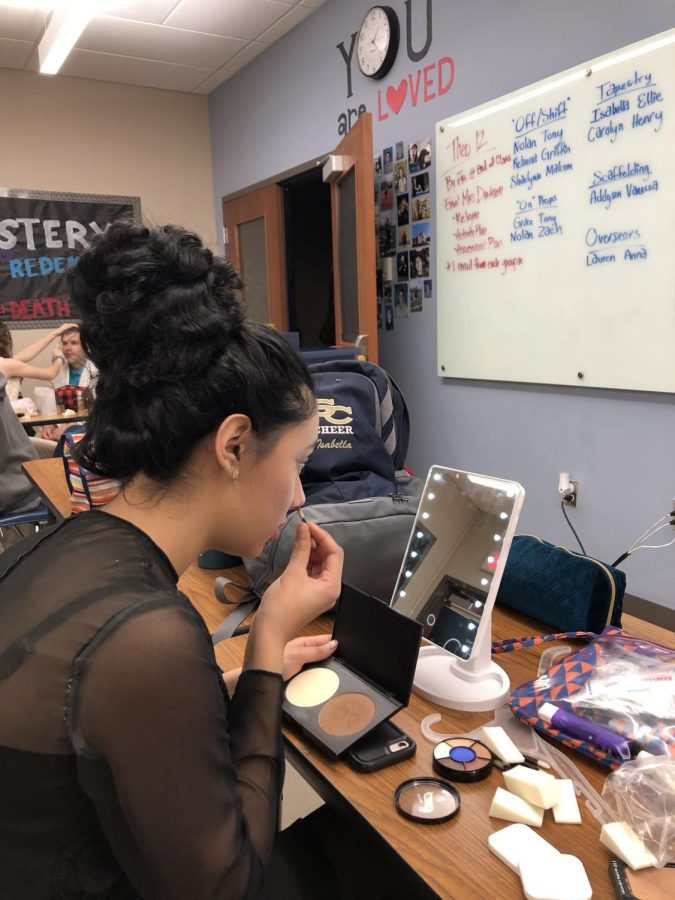 Senior Isabella Villagomez adds the final touches to her costume.